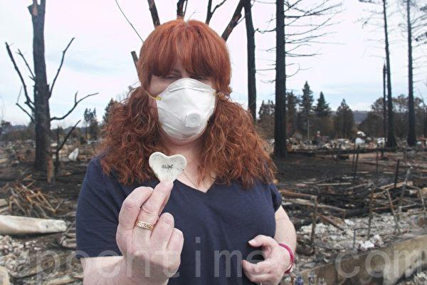 居民Susan Gray在被大火燒毀的家園廢墟中,找到了一個寫有「希望」(hope)字樣的心形飾品,期待重建家園。(李文淨/大紀元)