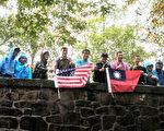 登上最頂峰的家長與部分青少年團員手持中華民國及美國國旗冒雨合影。(中華民俗藝術工作坊提供)