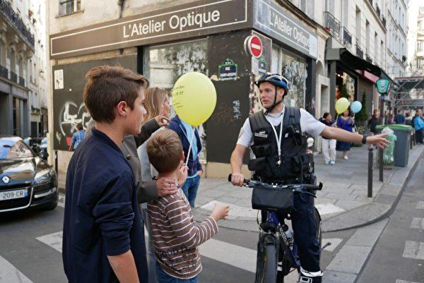 巴黎警察在给路人解释法轮功游行的目的。(张妮/大纪元)