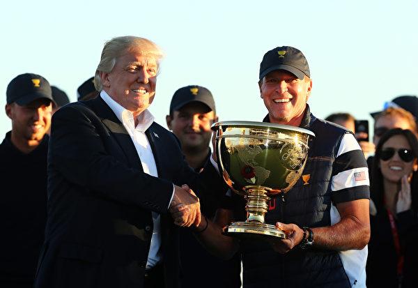 美国总统特朗普将总统杯冠军金杯颁发给队长史蒂夫‧史翠克代表的美国队。 (Elsa/Getty Images)