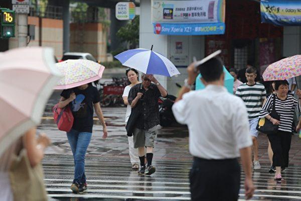 東北風增強,中央氣象局11日發布東部及北部等5縣市大雨特報,提醒民眾外出記得帶雨具。台北街頭午後也開始降雨。(中央社/提供)