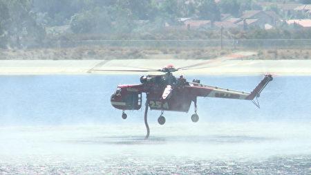 10月9日上午約9:20,在橙縣安納罕山(Anaheim Hills)旁,91號高速和石膏峽路(Gypsum Canyon Road)附近爆發了峽谷2號山火(Canyon Fire 2),威脅到山頂社區近千戶的家庭。圖為滅火直升機正在補充水源。(劉寧/大紀元)