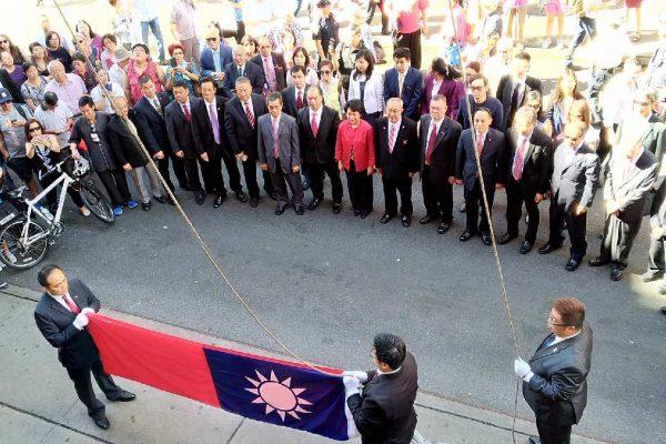 在庄严的国歌声中,护旗手把国旗展开,青天白日红旗在众人的注目下冉冉升向中华公所的上空。 (大纪元图片)