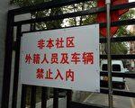 """北京石景山区公园北社区路口挂着""""不许外籍人员车辆进入""""的牌子,社区每天24小时有近50名保安等监控。(余文生提供)"""