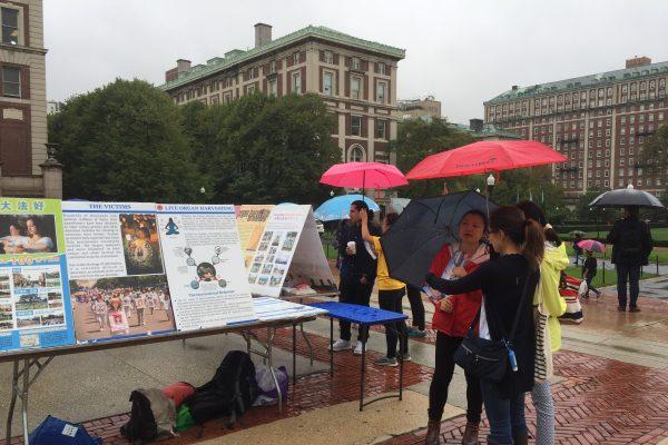 纽约哥伦比亚大学的法轮功学员9日在Low Library楼前冒雨举办讲真相活动。 (施萍/大纪元)
