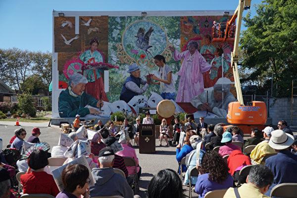 10月4日,宾州亚裔老人服务中心PASSi创办人及总裁崔英佳女士(Im Ja Choi) 在壁画揭幕剪彩前演讲。右上方艺术家Ann Northrup正在装上最后一片壁画。(肖捷/大纪元)