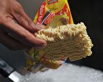 """2010年10月12日,印尼雅加达的一个街食摊位正准备煮""""Indofood""""食品公司生产的即时面。(BAY ISMOYO/AFP/Getty Images)"""