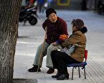 在北京召開的十九大期間, 一隊隊戴紅袖章的「志願者」大媽、大爺們也正在街頭東張西望。 (WANG ZHAO/AFP/Getty Images)