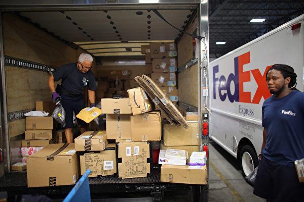 亚马逊正测试一项新的送货服务,专家担心这将影响优比速(UPS)和联邦快递(FedEX)等业者的商机。图为佛罗里达,联邦快递的工作人员正准备运送亚马逊公司的商品。(Joe Raedle/Getty Images)