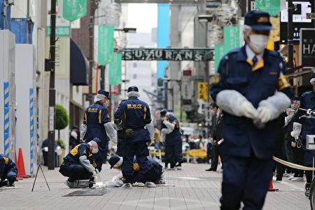日本是世界上犯罪率最低的国家之一。因为犯罪率低,而且警力充足,所以该国警察会没事找事做。图为在东京调查案件的警察。(STR/AFP/Getty Images)