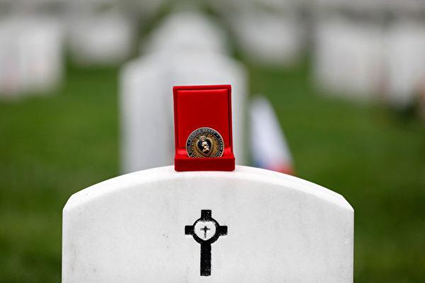 根据关系的亲疏,人们会在士兵墓碑上放置不同金额的硬币。(Aaron P. Bernstein/Getty Images)