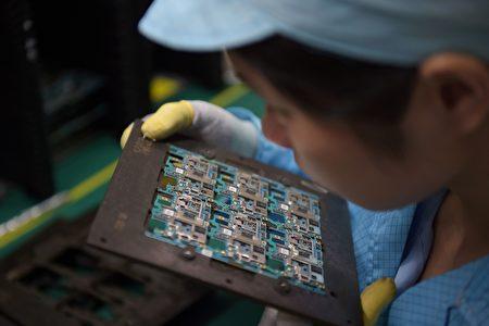 """川普政府已开始对中国的知识产权问题进行""""301调查"""",调查或许是为11月访华做前期准备。图为一名东莞工人正在查看手机芯片。      (NICOLAS ASFOURI/AFP/Getty Images)"""