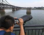 中朝邊境,遼寧丹東鴨綠江斷橋上一人用望遠鏡觀察對岸的朝鮮一方。   ( GREG BAKER/AFP/Getty Images)