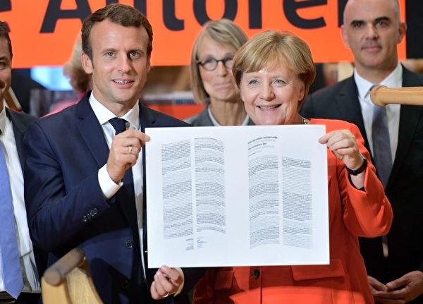 德国总理默克尔和法国总统马克隆双双出席书展开幕式,展示用传统印刷术印制的《人权宣言》。 (Thomas Lohnes/Getty Images)