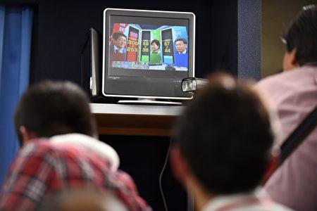 10月22日,日本民众收看关于日本众议院选举的新闻报导。 (TORU YAMANAKA/AFP/Getty Images)