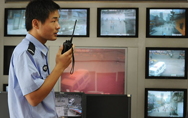图为2009年7月12日,安徽省合肥近郊一名警察在使用对讲机,其背后是路灯监控摄像机返回的镜头。中国每年出现数以万计的民众抗议事件,比较常见的原因是政府腐败和官方滥用权力。 (AFP/AFP/Getty Images)