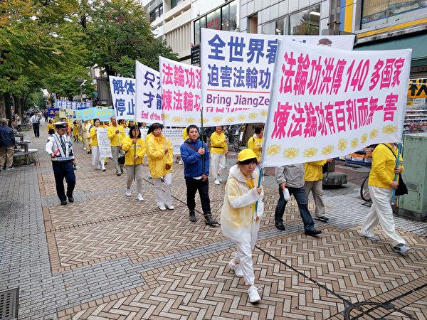 10月14日,日本法輪功學員在橫濱舉行了反迫害遊行活動,真相條幅吸引了很多路人觀看,中共活體摘取法輪功學員器官販賣牟利的罪行受到當地民眾的關注。(盧勇/大紀元)