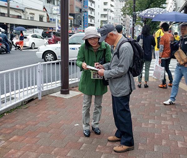 10月14日,日本部分法轮功学员在横滨举行了反迫害游行活动,真相条幅吸引了很多路人观看,中共活体摘取法轮功学员器官贩卖牟利的罪行受到当地民众的关注,很多人签名支持法轮功学员反迫害。(卢勇/大纪元)