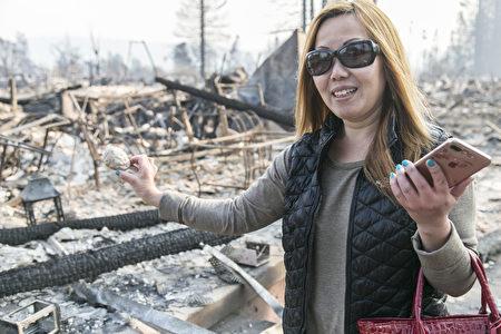 華人Karen Tang在灰燼中找到了自己喜愛的天使雕像,非常高興,感謝神在保護她。(曹景哲/大紀元)