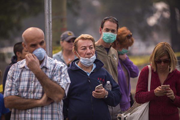 北加州大火產生的煙塵嚴重,很多人外出都戴著口罩。(David McNew/Getty Images)