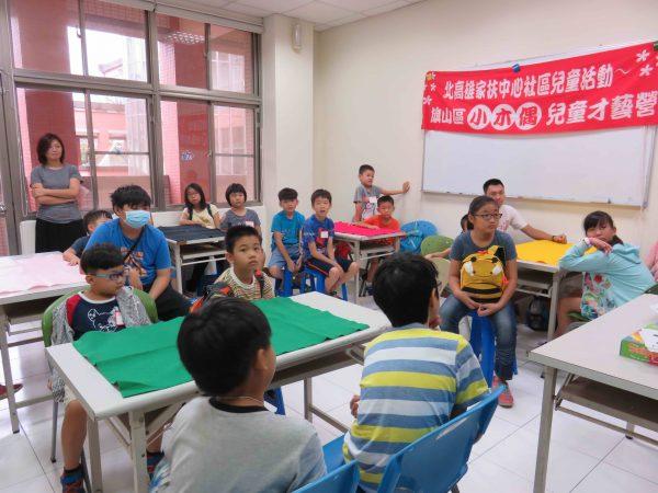 桌遊講師劉峻誠講解桌遊規則 小朋友聚精凝神聽著並興緻勃勃像老師提問題。桌遊簡單而言就是指不插電並可以在桌上進行的遊戲,大部份可分為兩種類型,一種是紙牌遊戲,另一種是圖版遊戲。(北高家扶中心提供)