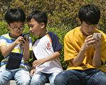 图为韩国青少年在看手机。(全景林/大纪元)