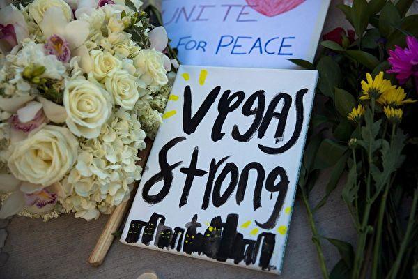 在拉斯维加斯枪击案现场,民众为遇难者献上的花束和悼词:拉斯维加斯要坚强。(Drew Angerer/Getty Images)