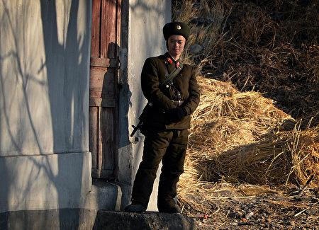 因糧食普遍不足,朝鮮出現士兵搶奪老百姓糧食的事件,而且經常發生。圖為一名朝鮮士兵於2013年12月16日在鴨綠江岸邊站哨。(MARK RALSTON / AFP)