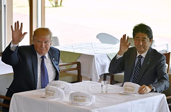 2017年11月5日,美国总统川普与日本首相安倍晋三,在日本川越市一处高尔夫球场向在场媒体工作人员挥手。(FRANCK ROBICHON, Laurent FIEVET / POOL / AFP)