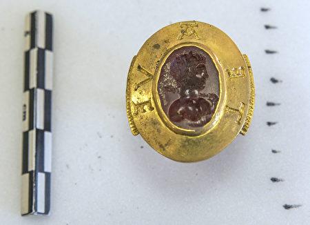"""发掘出的一枚镶有镌刻着头像的红宝石的金戒指,戒指上雕刻着""""Avete""""。( Credit Alexis Grattier / University Lumiere Lyon II / AFP)"""
