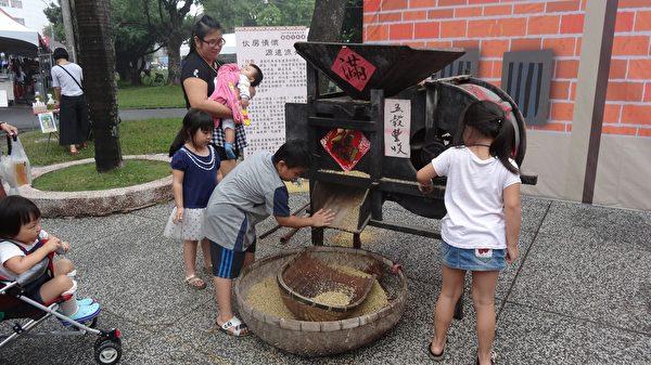 民众在农具体验区操作传统的稻米打榖机。(曾晏均/大纪元)