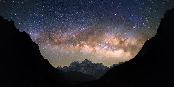 """在多雪的山的明亮和生动的银河星系。 美丽的繁星满天的夜空似乎是在一个""""碗""""之间的映衬的山丘。"""