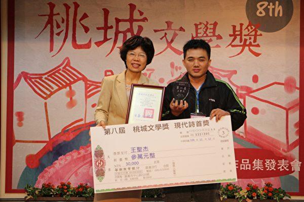 _現代詩組第一名王聖杰。文化局局長黃美賢(左)頒給獎金參萬元、獎座乙座。(李擷瓔/大紀元)