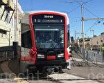 11月17日,第一辆Muni新型轻轨列车带着红花驶出车库。(李文净/大纪元)
