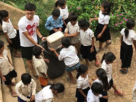 台湾国防医学院团员杨大庆在Preak Kmeng小学带着学生落实垃圾分类,维持校园好环境。(青年发展署提供)