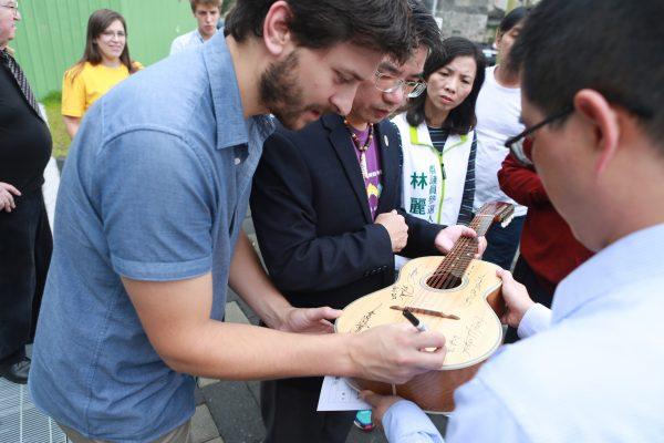 音乐家在江市长的小提琴上签名留念。(曾汉东/大纪元)