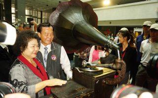 陈菊(左)与收藏家林本博(右)一同让这座90岁月的英国留声机发出优美乐音。(李怡欣/大纪元)