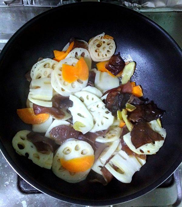冷鍋倒入冷油,再把蓮藕和木耳、紅蘿蔔倒入鍋中,加入30cc的水,開中火炒熟。(圖:奧莉薇小姐/大紀元)