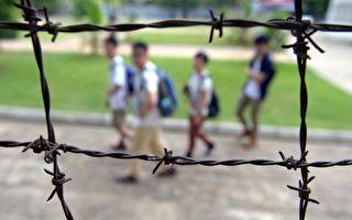 柬埔寨的吐斯廉屠殺博物館由前赤棉的集中營監獄改建而成,揭露共產暴政殘害人民的罪惡。圖為人們從該監獄的鐵絲網外面走過。(TANG CHHIN SOTHY/AFP/Getty Images)