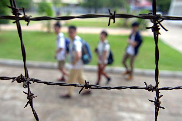 柬埔寨的吐斯廉屠杀博物馆由前赤棉的集中营监狱改建而成,揭露共产暴政残害人民的罪恶。图为人们从该监狱的铁丝网外面走过。(TANG CHHIN SOTHY/AFP/Getty Images)