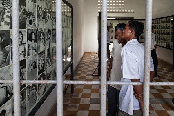 图为参观者在观看博物馆里展示的受难者的照片。(Omar Havana/Getty Images)