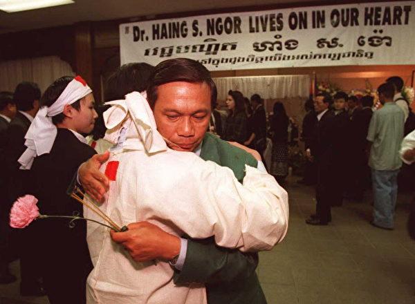 1996年2月25日,奥斯卡最佳男配角获得者、柬埔寨裔演员Haing S. Ngor在洛杉矶遇害身亡。图为3月8日在追思会上,Ngor曾扮演过的记者Dith Pran安慰其侄女Wathana Sarun。(KIM KULISH/AFP/Getty Images)