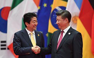 圖為G20期間安倍晉三與習近平握手。     (GREG BAKER/AFP/Getty Images)