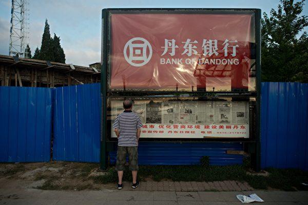 圖為2017年7月5日,「丹東銀行」設立在中國丹東市的商業廣告牌。(NICOLAS ASFOURI/AFP/Getty Images)
