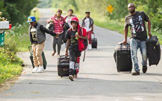 8月4日自称是来自海地的一组人在纽约州,准备通过美加边境,非法进入加拿大。(GEOFF ROBINS/AFP/Getty Images)