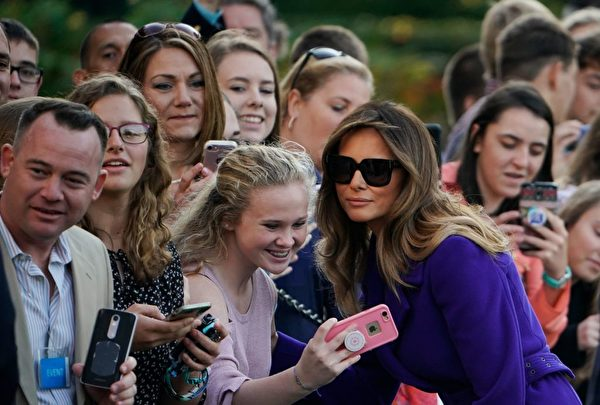 US First Lady Melania Trump poses for a photo with a guest as she and US President Donald Trump make their way to board Marine One before departing from the South Lawn of the White House on November 3, 2017 in Washington, DC, embarking on a 11-day tour of Asia. / AFP PHOTO / MANDEL NGAN (Photo credit should read MANDEL NGAN/AFP/Getty Images)