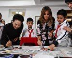 梅拉尼娅学习手握中国毛笔。(GREG BAKER/AFP/Getty Images)