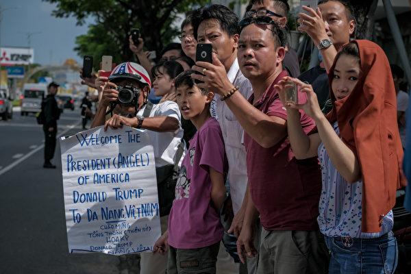 川普抵达越南时,也受到当地民众欢迎,很多民众在街道两边迎接川普,打出欢迎标语,用手机拍照。(Linh Pham/Getty Images)