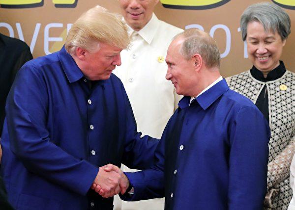 在亚太经合组织会议中,川普和穿同样传统服装的普京握手。(MIKHAIL KLIMENTYEV/AFP/Getty Images)