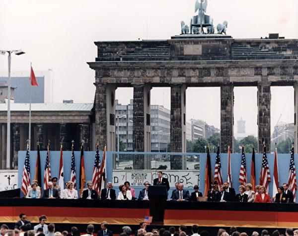 """1987年6月12日,里根总统访问西柏林时,在勃兰登堡门的柏林墙前发表""""推倒这堵墙""""演说。(公有领域)"""